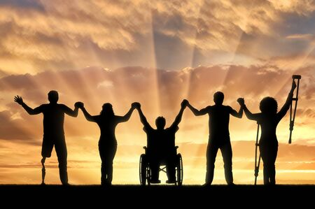 Invalids on crutches and in wheelchair and prosthesis in foot and healthy people standing on sunset background and holding hands. Concept happy disabled