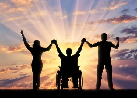 Disabled in wheelchair and healthy people holding hands on sunset background. Concept happy disabled