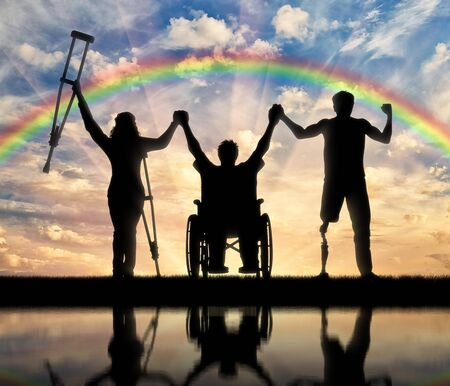 unprotected: Invalids on crutches and in wheelchair and prosthesis in foot standing on rainbow background and holding hands. Concept happy disabled