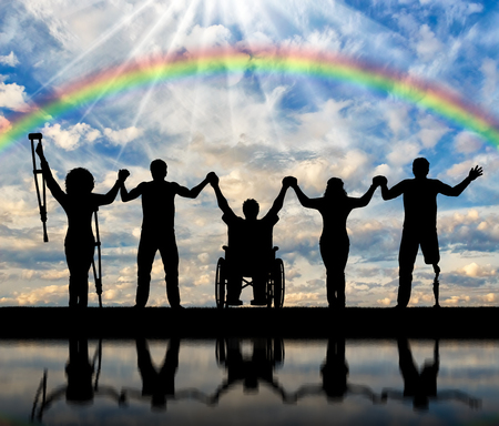 Invalids on crutches and in wheelchair and prosthesis in foot and healthy people standing on rainbow background and holding hands. Concept happy disabled Stock Photo