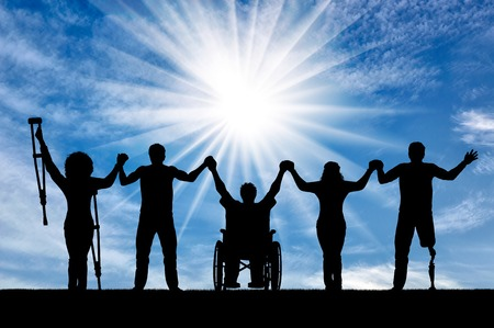 Invalids on crutches and in wheelchair and prosthesis in foot and healthy people standing day and holding hands. Concept happy disabled Stockfoto