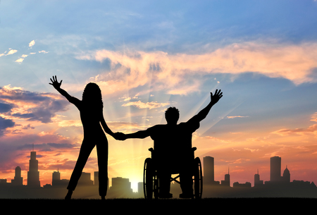 Happy disabled person in a wheelchair, holding his hands Maritime Day girlfriend. The concept of happy people with disabilities and the family Stock Photo