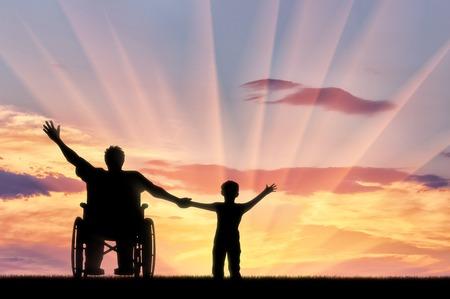 persona feliz: persona con discapacidad feliz en silla de ruedas para el hijo de retención mano y feliz en sunset.Concept feliz personas con discapacidad y la familia