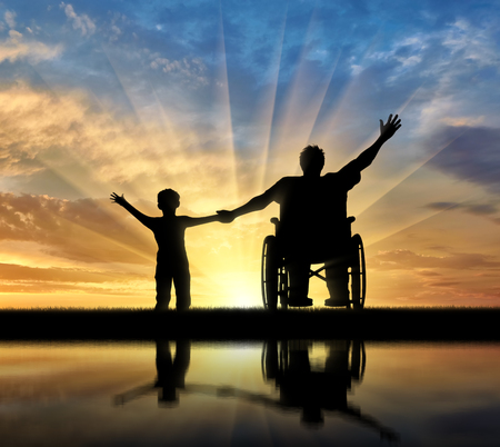Happy disabled person in wheelchair hold son for hand and they happy and with their reflection in water on sunset. Concept happy disabled and familymily Stock Photo