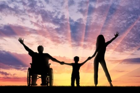 persona feliz: persona con discapacidad feliz en silla de ruedas con su familia de la mano en la puesta del sol. Concepto feliz personas con discapacidad y la familia Foto de archivo