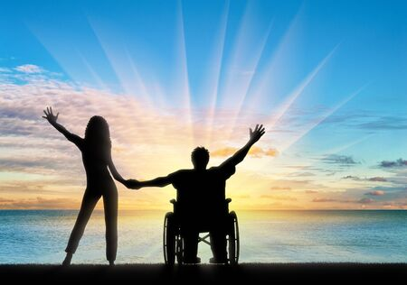 unprotected: Happy disabled person in wheelchair holding hand girlfriend by sea day. Concept happy disabled and family Stock Photo