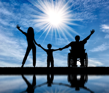 Happy disabled person in wheelchair with his family holding hands and reflection in water in afternoon. Concept happy disabled and family