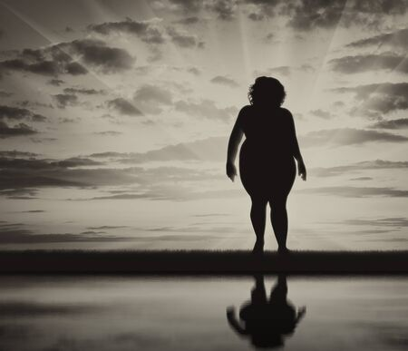 excess: Fat woman standing near water and reflection background of sky. Concept obesity