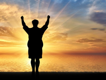 indecisive: Happy fat man with raised arms near sea on background sunset. Concept obesity Stock Photo