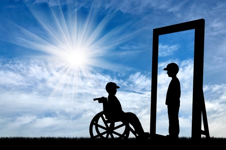 capable: disabled child in a wheelchair and his reflection in mirror of a healthy baby boy on a background of sky Stock Photo