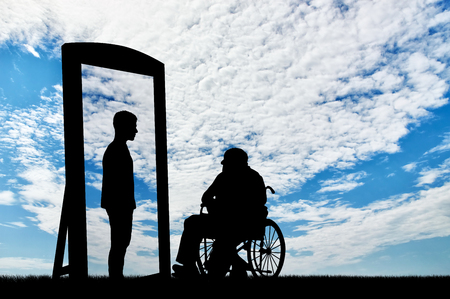 disabled man in a wheelchair and his reflection in mirror of a healthy man against the sky. disabled rehabilitation concept