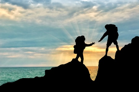 Climber reaches out to his partner by helping each other. concept of teamwork Stock Photo