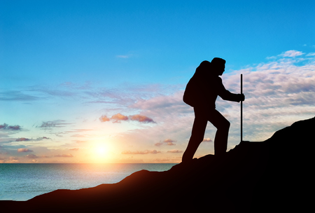 purposeful: Ascent climber on top of a mountain on a background of sea sunset. Concept of challenge