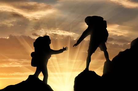 reaches: Climber reaches out to his partner by helping each other. Concept of teamwork and trust