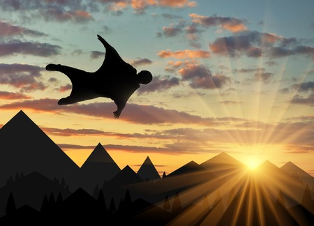 Wingsuit extreme sports. A man in a suit for wingsuit flying, mountains in background at sunset Lizenzfreie Bilder