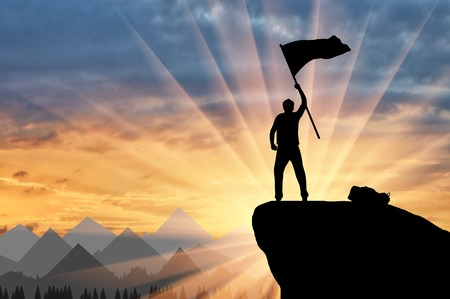 彼の手のフラグと山の頂上に登山者のシルエット。? の力と成功の概念 写真素材