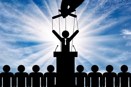 Politician is a puppet and a hand is pulling him by strings. Concept of manipulation and covert control Stock Photo