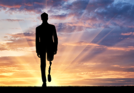 Walking disabled with a prosthetic leg at sunset Stockfoto