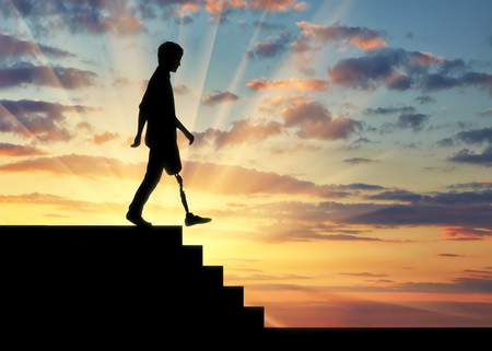Disabled person with a prosthetic leg descends down the stairs at sunset