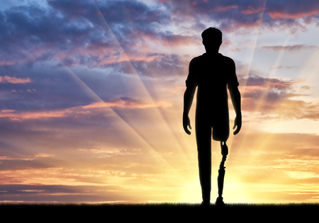 rehabilitated: Disabled person with a prosthetic leg at sunset