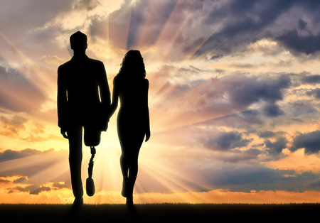 Concept of support and assistance to people with disabilities. Disabled person with a prosthetic leg, walking with a woman holding hands at sunset Stock Photo
