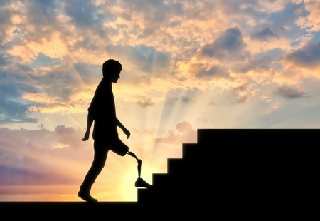 Disabled Walking with a prosthetic leg climbs the stairs at sunset Banco de Imagens