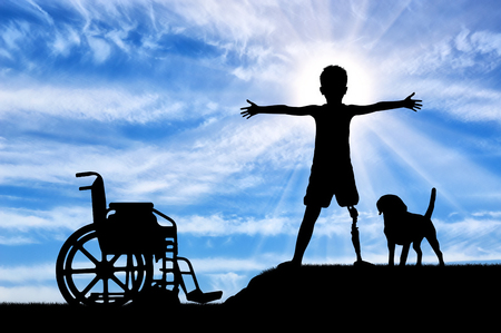 Children with disabilities concept. Happy disabled boy with a prosthetic leg standing near a wheelchair and his friend dog