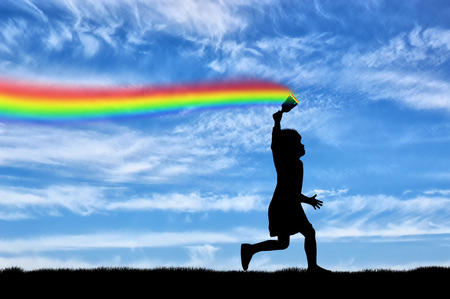 Childhood concept. The child with brush in hand, runs, and draws a rainbow in the sky