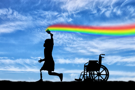 Childrens disability concept. The child has a disability with a prosthetic leg with a brush in hand, runs, and draws a rainbow in the sky and next to wheelchair