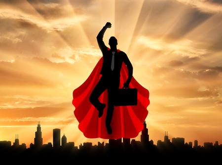 スーパーマンの実業家のスーパー ヒーロー。都市の夕暮れ空を飛んでブリーフケースとスーパーマン ビジネスマンのシルエット