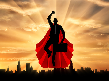 Superman businessman superhero. Silhouette of a superman businessman with a briefcase flying in the sky over the city at sunset Stockfoto