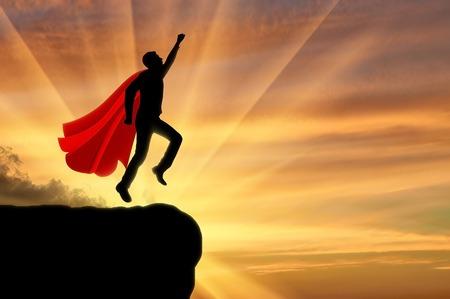 Superman businessman superhero. Silhouette of a businessman in the image of a superman flies in the sky at sunset Reklamní fotografie