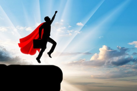 Superman businessman superhero. Silhouette of a businessman in the image of a superman flies in the sky with a briefcase on dawn Stock Photo