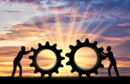 Silhouette of two people who want to connect the two gears in a single mechanism. Business team concept Stok Fotoğraf