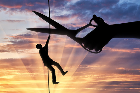 Silhouette of a businessman climbs on a tightrope and a hand with scissors intends to cut a rope. Concept of risks in business