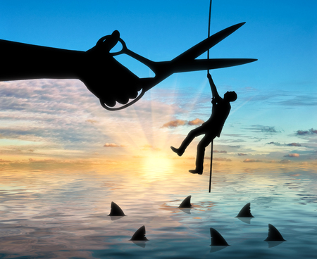 meanness: Silhouette of a businessman climbs a rope above the sharks and a hand with scissors intends to cut the rope. The concept of competition and risks in business