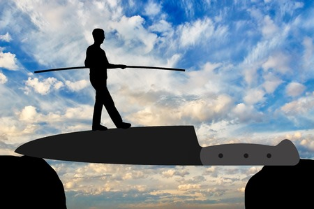 Silhouette of a man walking on a knife blade balances. Concept of strength and determination in business Stock Photo