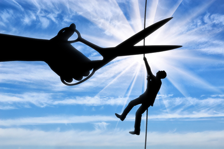 Silhouette of a businessman climbs on a tightrope and a hand with scissors intends to cut a rope. The concept of a rival in business Stock Photo