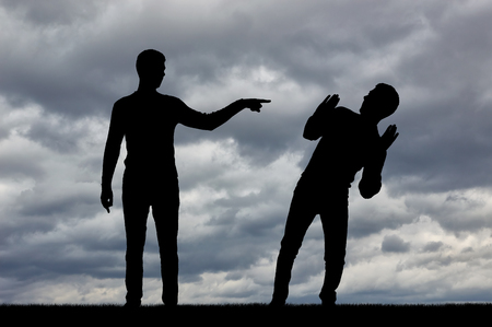 Silhouette of a man showing a finger at another man. The concept of prosecution in society Stock Photo