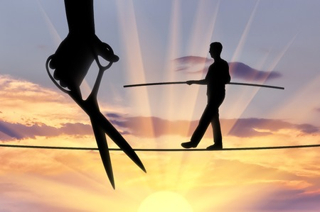 Silhouette of a businessman walking on a tightrope balances and a hand with scissors intends to cut the rope. The concept of meanness in business