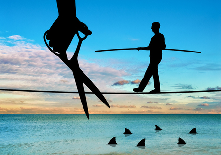 Hand with scissors intending to cut the rope where the businessman is teetering over the sharks. The concept of competition and risk in business Stock Photo