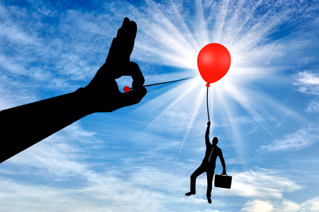 Silhouette of a man in the air clinging to a balloon and a hand with a needle wants to burst it. Concept of meanness and treachery in business