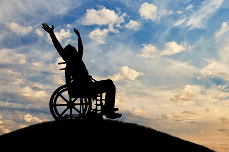 Happy disabled person in a wheelchair with arms raised. The concept of happy people with disabilities