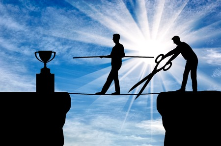 A business competitor with big scissors in his hands intends to cut the rope along which the businessman goes to the trophy. The concept of envy of rivals to the success of another person Stock Photo