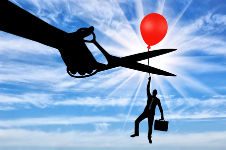 A man climbs up holding onto a balloon, and a hand with scissors intends to cut it off. The concept of risk Stock Photo