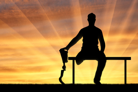 Silhouette of a man holding the hand of his prosthetic leg, sitting on the bench. The concept of people with prosthetic legs