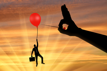 Silhouette of a man in the air clinging to a balloon and a hand with a needle wants to burst it. Concept of risks and complexities in business Stock Photo