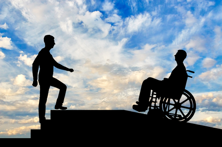 A disabled person in a wheelchair climbs up the ramp, and healthy man on the stairs. The concept of helping the disabled to move