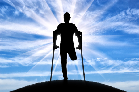 Silhouette of a man with an amputated leg standing with crutches outdoors. The concept of people with disabilities
