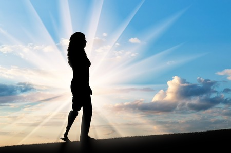 A silhouette of a woman with a prosthetic leg going up on the slope. The concept of rehabilitation of people with disabilities